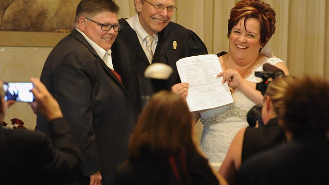 Jayne Rowse, far left, and April DeBoer, right, show off their wedding certificate with Judge Bernard Friedman.