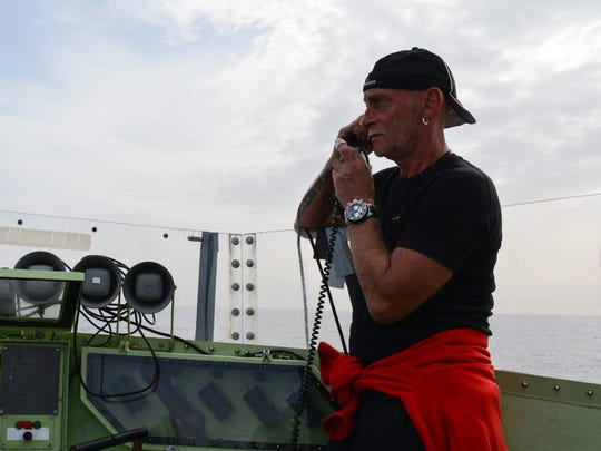 Captain Christian Brensing talks on the radio to other rescue organizations working off the coast of Libya.