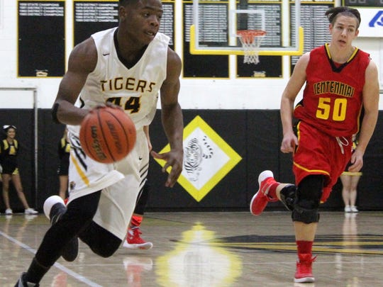 Dee Smith, left, races past Centennial's Bo Glines on Saturday afternoon. Centennial defeated Alamogordo 77-59.