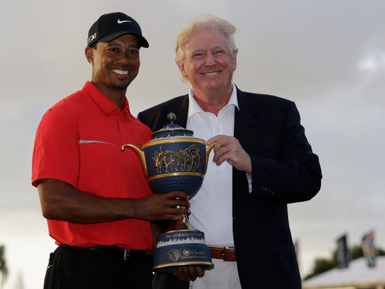 In a file phote from 2013, Tiger Woods stands with Donald Trump as he holds the Gene Sarazen Cup for winning the Cadillac Championship in Doral, Fla.
