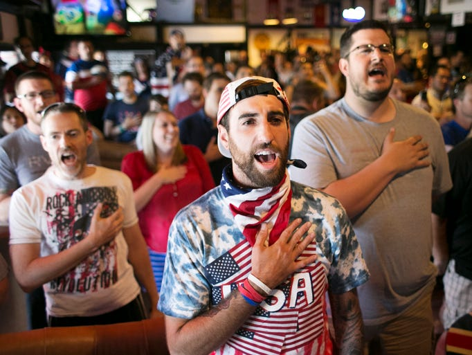 Bo Mitchell of Phoenix, recites the National Anthem while watching the World Cup match between the USA and Belgium, at the George and Dragon English Pub in Phoenix on Tuesday, July 1, 2014. Belgium beat USA 2-1 eliminating USA.
