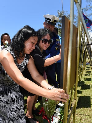 """Clara Mortera, left, places a photo on the portrait of her late husband, Sgt. Siegfred """"Dove"""" Mortera, as his mother, Gloria Mortera, reaches to touch the portrait during the annual Peace Officers' Memorial Service on May 27, 2015. Siegfred Mortera died on Feb. 14, 2015, died after collapsing during SWAT training."""