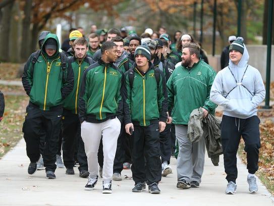 The Brockport football team marches to a pep rally