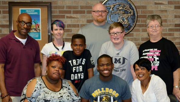 Denzel Tinsley (seated, middle) is pictured with family,