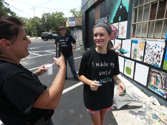 Artist Kollet Probst takes a photo of Kylea Verheyen, 11, as she pairs up with nearly 70 children to complete a mural on the Grace Mission Episcopal Church in Frenchtown on Monday, June 4, 2018.