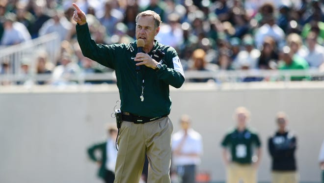 Head coach Mark Dantonio pumps up the crowd during the Green and White Spring Game on Saturday, April 23, 2016 at Spartan Stadium.