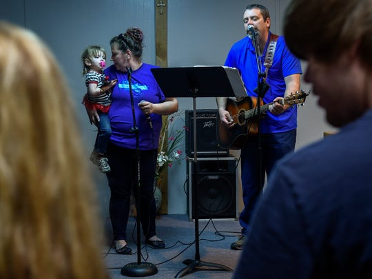 Marcella Robertson holds her daughter Shiloh as she sings with her husband, Ben, at the beginning of fellowship at the Celebrate Recovery program in Dover, Tenn., on Friday, Feb. 17, 2017.