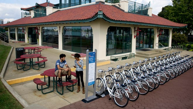 Aydin Harrison, left, and Rebekah Ragland of Evansville register to use the Upgrade Bike Share at zagster.com/upgrade at the Pagoda Station Monday afternoon. The new bike share program allows members to rent bicycles from seven different stations around town.