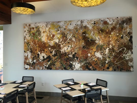 """""""Sweet Smell of Success"""" artwork made with paint and spices by Matthew Ruddy VIII hangs on the wall at 9 East in Springdale."""