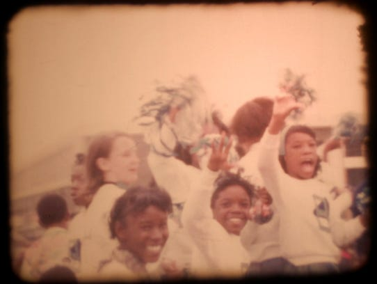 A home movie image shows cheerleaders from St. Bernard's