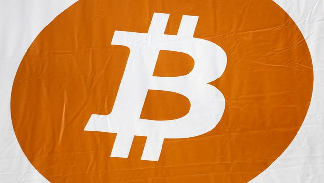 """In this Monday, April 7, 2014, file photo, a bitcoin logo is displayed at the Inside Bitcoins conference and trade show in New York. The bitcoin miner NiceHash says it is investigating a security breach and the theft of the contents of the NiceHash """"bitcoin wallet."""""""