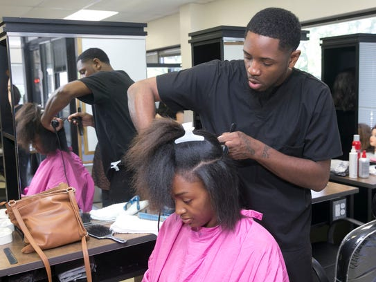 Erik Smith, Neptune, gives a haircut to Shadiah Neal,