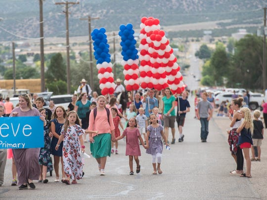 Participants walk along Midvalley Road during the Pioneer Day parade in Enoch Tuesday, July 24, 2018.