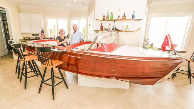 "Dave and Michelle Sylvester, with their dog Pretty Girl, stand behind their ""Red Queen"" Century boat bar with custom granite countertops, built by Dave Sylvester for their lakeside home."