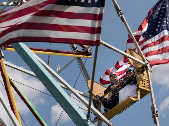 (from left) Sarah Asfare and her sister Bushra Asfare ride the ferris wheel at the Passaic County Fair on Saturday, August, 19, 2017.