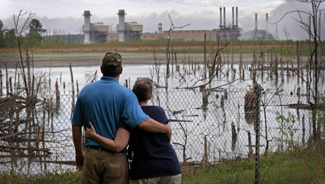 Bryant Gobble, left, hugs wife Sherry as they look from their yard across an ash pond full of dead trees toward Duke Energy's Buck Steam Station in Dukeville, N.C., near Salisbury.