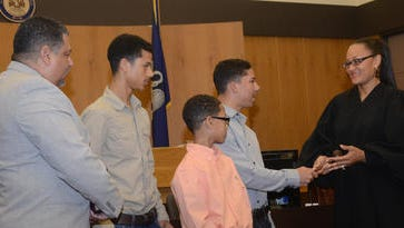 New 9th District Judge Monique Rauls (right) receives a gavel from her son, Payden Rauls (second from right), and other members of her family today as she took her oath of office. From left are her husband, James Rauls III, and sons Ashton, Carson and Payden.