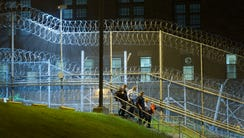 Corrections officers walk next to a fence covered in