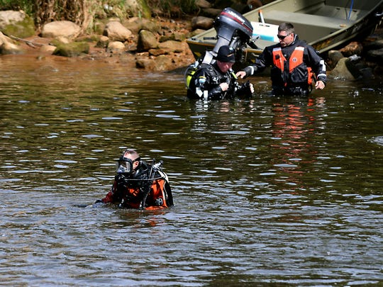 Divers head in to search the Grand River near the Brenke