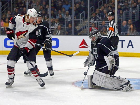 Los Angeles Kings goalie Jack Campbell (1) blocks the puck as Arizona Coyotes center Christian Dvorak (18) watches during the first period of an NHL hockey game in Los Angeles on Thursday, March 29, 2018. (AP Photo/Reed Saxon)