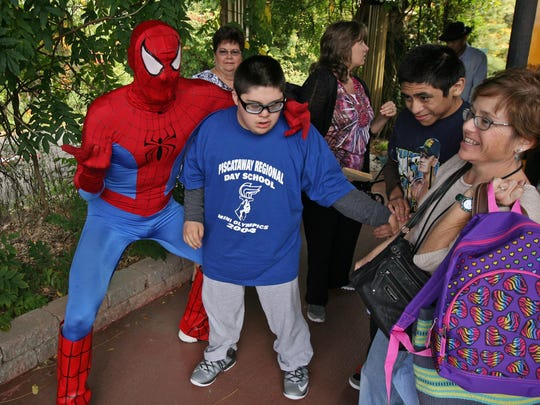Joel M., a student from Piscataway Regional Day School, is greeted by Spiderman, as students arrive for the party. The Greek hosts an annual Oktoberfest for the disabled community free of charge, at The Greek's Playland/Stone Museum, October 15 2014 Jamesburg NJ. Photo by Kathy Johnson BRI EST 1016 The Greek's Oktoberfest