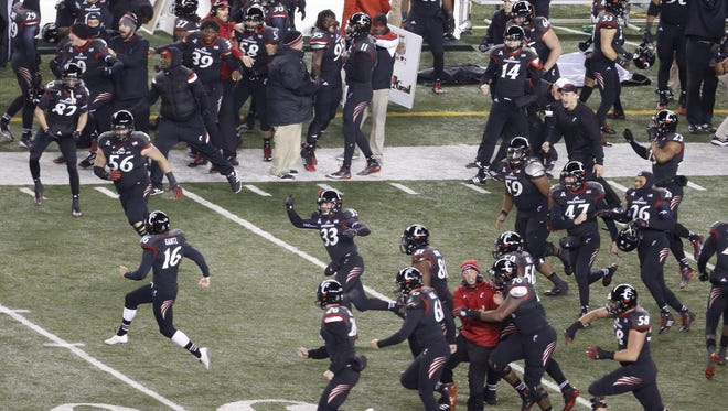 University of Cincinnati players storm the field after Andrew Gantz (16, front left) kicked a 47-yard field goal in the final seconds against East Carolina.