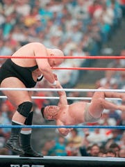 King Kong Bundy picks on someone, umm, not quite his own size in a six-man tag-team match.