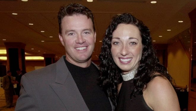 In this March 1, 2001 file photo, Six-time Olympic gold medalist swimmer Amy Van Dyken, right, and Denver Broncos punter Tom Rouen pose before going into the Colorado Sports Hall of Fame dinner in Denver. Van Dyken has a severed spine after an accident on her all-terrain vehicle in Arizona. A hospital spokeswoman didn't provide details Monday on the injuries. The swimmer was hurt Friday night, June 6, 2014,  and told emergency workers at the scene she could not move her toes or feel anything touching her legs.