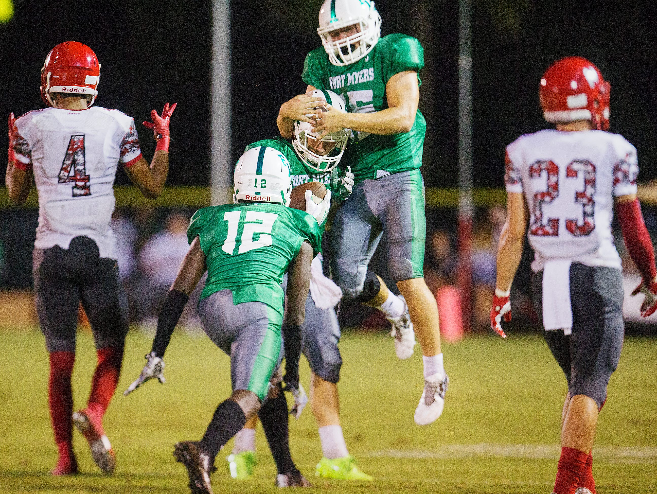 Fort Myers High School players celebrate an interception by Ben Stobaugh, center, against North Fort Myers during first quarter play Friday at Fort Myers High School.