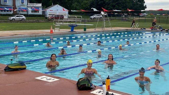 Greenwood Coach Don Lemieux, left, and his swimmers take a break during training sessions at the outdoor Greenwood Pool in Gardner. With the WPI pool closed due to the COVID-19 pandemic, the Greenwood Memorial Swim Team has been using the outdoor pool as its training facility since June 13.