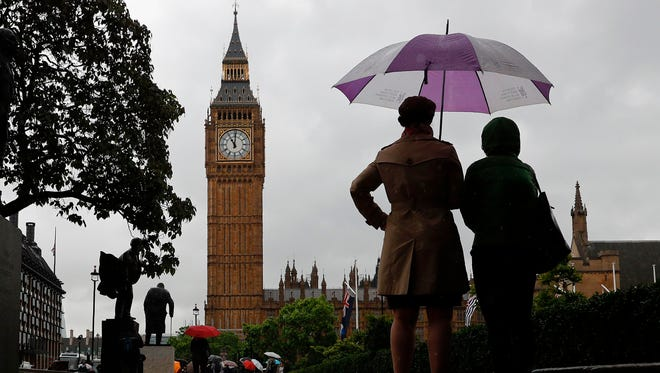 People shelter from the rain beneath an umbrella as they observe a minutes' silence near the Elizabeth Tower, commonly referred to as Big Ben, at the Houses of Parliament in London June 6, 2017, in memory of the victims of the June 3 terror attacks.