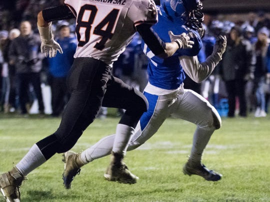 Amherst flanker Chris Andersen eludes Ed Bonikowske of Iola-Scandinavia to score a touchdown in the fourth quarter Friday night.