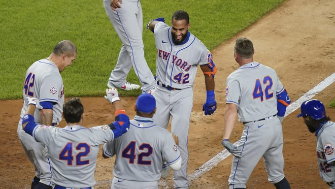 The New York Mets' Amed Rosario scores as teammates celebrate following his walkoff home run off New York Yankees relief pitcher Aroldis Chapman in the seventh inning of the second baseball game of a doubleheader, Friday at Citi Field. All players and management staff are wearing No. 42 as a tribute to baseball great Jackie Robinson.