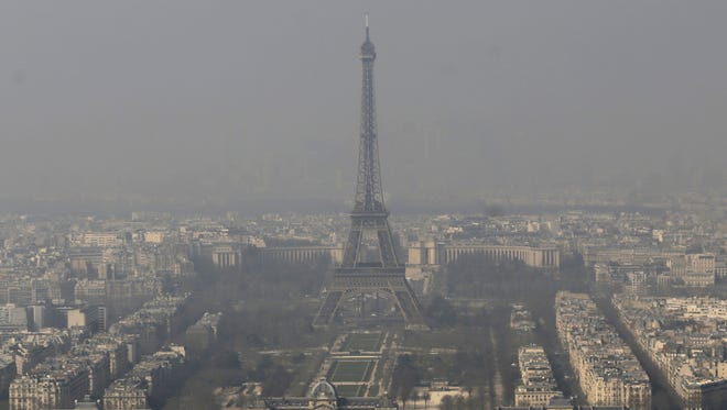 The Eiffel Tower is photographed through the smog in Paris. Police have lowered speed limits and ordered a halt to trash burning as part of emergency measures triggered by a surge in air pollution.