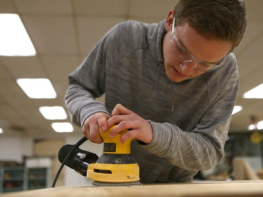 Lake View's Elliot Peterson sands a wooden table he built with a partner inside the Ag Department on Feb. 2, 2018.