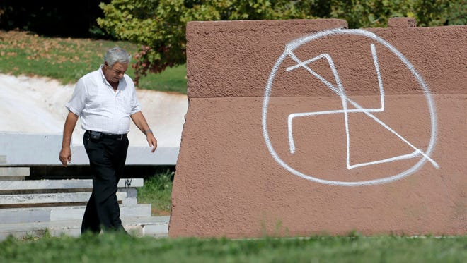 A pedestrian passes anti-fascist graffiti in Athens on Sept. 30, 2013. Greece's government is submitting legislation to Parliament aimed at cutting state funding to the extreme right-wing Golden Dawn party, whose leadership was arrested over the weekend on charges of acting as a criminal organization.