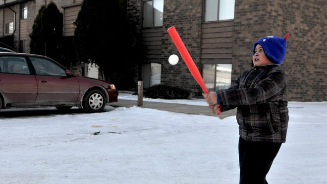 Dorien Erickson, 6, plays whiffle ball with his mom Esther in the parking lot of Tower Heights Apartments in Sauk Rapids