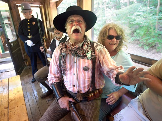 "Bob Alexander reacts after Karen Seibel places fake money into his shirt like a stripper while the ""bad guy"" participates in a train robbery on Saturday. Alexander joined other outlaws and lawmen reenactors  for the monthly event hosted by Steam Into History."