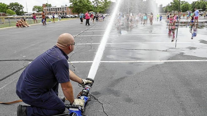"Norwich Township Fire Department Lt. Jeff Woodward adjusts a hose nozzle as firefighters from Station 81 provided a cool activity for children on a warm summer afternoon Aug. 12 at Hilliard Heritage Middle School. The city's Hilliard Family Aquatic Center and Clyde ""Butch"" Seidle Community Pool have been closed for the 2020 season because of COVID-19 coronavirus pandemic."
