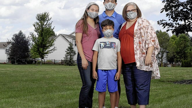 Emily DePaul is pictured Aug. 7 with her three children, Isaac Gil, 8, Isabela Gil, 19, and Marc Gil, 18, at their home in Lewis Center. DePaul's family was quarantined with the COVID-19 coronavirus all at the same time, exhibiting a variety of symptoms and severities, but all four have recovered.