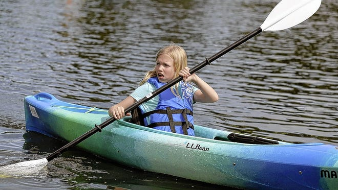 Camper Adalynn Hopper, 9, looks toward the shore as she paddles her kayak across the water as part of Columbus and Franklin County Metro Parks' summer camp program June 17 at Homestead Metro Park in Hilliard. The camps were able to resume but with modifications due to the COVID-19 coronavirus pandemic.