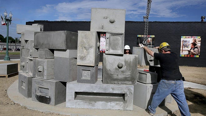Doug Gehring, production manager at Lindsay Precast, guides one of 63 concrete televisions into place with the help of a crane as artist Katherine Stanek watches in Canton.