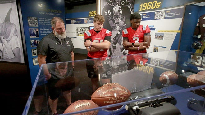 """Alliance High School head football coach Seth Whiting along with his players Andrew Datz (middle) and Brandon Alexander view items from early history of the NFL during a tour of the Pro Football Hall of Fame. The Hall hosted an initiative called """"Build the Bridge"""" -- a program created by Kahari Hicks, an assistant  football coach at Cleveland Heights High School."""