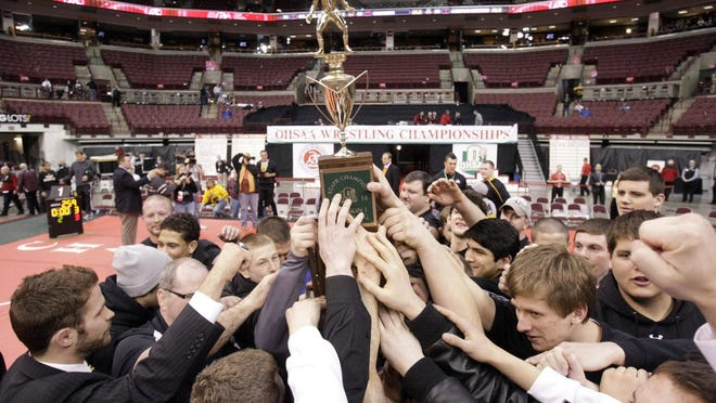 The Perry wrestling team hoists the state championship trophy at the 2014 OHSAA State Individual Wrestling Championship.