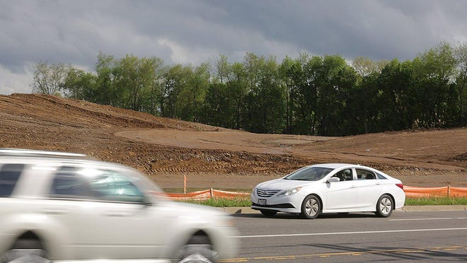 Cars buzz by the dirt being moved for development of senior housing and a Meijer store in Jackson Township along Fulton Drive NW.
