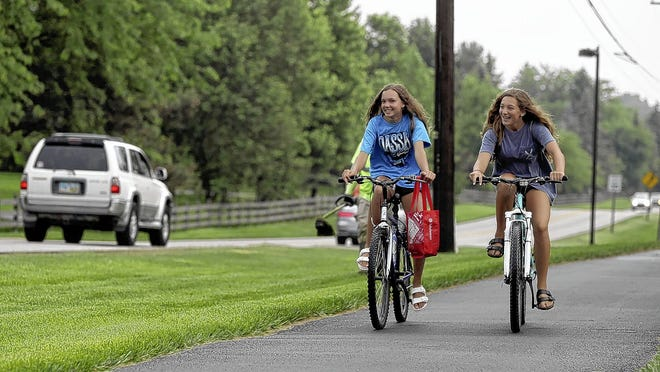 Maysen Ernst (left) and Kate Basham, both 14-year-old Dublin residents, travel along the shared-use path on the south side of Glick Road on June 4 in Dublin.