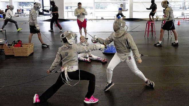 Sahana Ramakrishnan (left), 9, of Dublin and Sasha Suspitsyna, 11, of Upper Arlington face off during a July 9 class at Columbus Fencing & Fitness in Dublin.