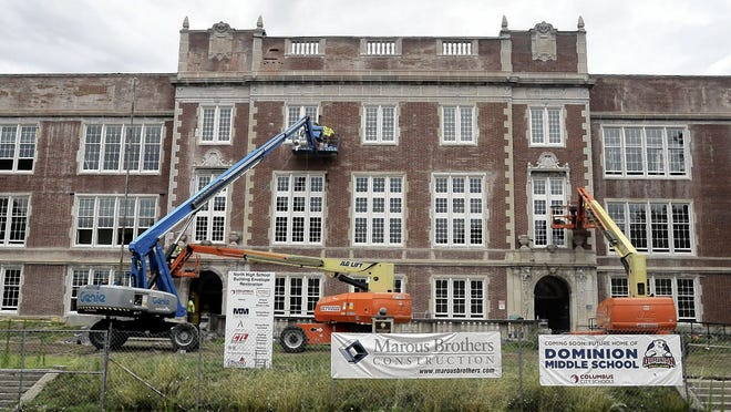 Construction crews working on reinstalling bricks around new windows July 22 at the longtime Columbus North High School building, which is being converted into the new home of Dominion Middle School.