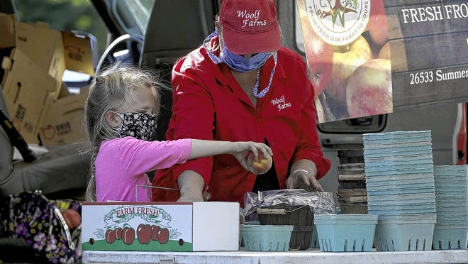 Reagan Casto, 7, helps sort peaches with her grandmother, Jeanne Woolf, at the Woolf Farms vendor booth Aug. 20 at the New Albany Farmers Market.