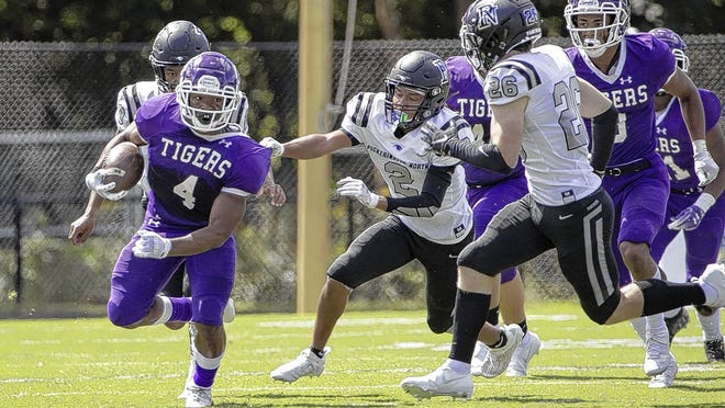 Pickerington Central's Nick Mosley heads upfield ahead of Pickerington North's Brian Dickerson on Aug. 30. The Tigers won the nonl-eague game 35-9 and will play at Newark on Friday, Sept. 4.